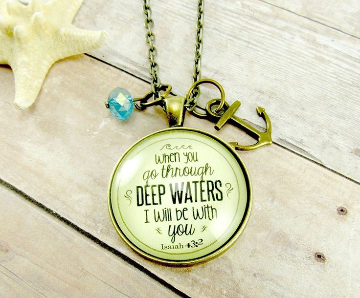 """A bronze-colored glass pendant quoting the Bible verse, Isaiah 43:2: """"When you go through deep waters,…"""