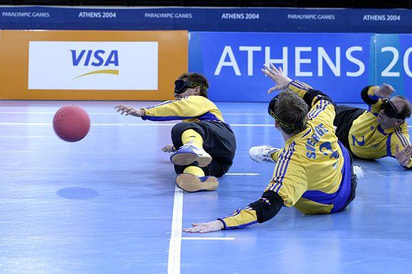 Três atletas, usando vendas, estão deitados na quadra, durante uma partida de…