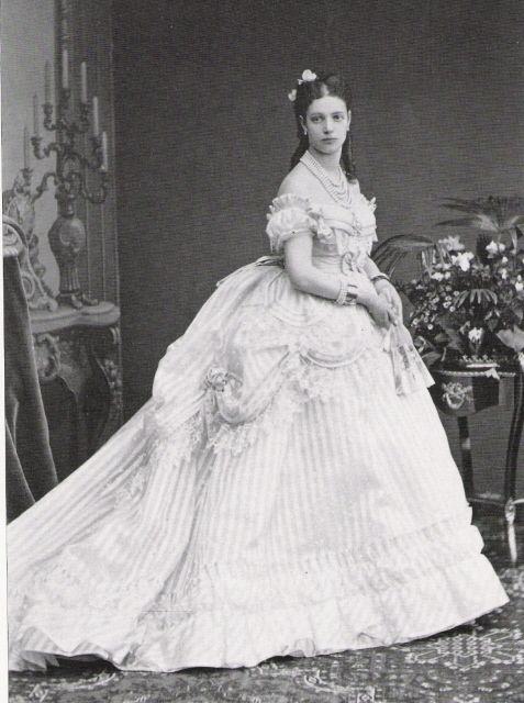 Maria Feodorovna wears an elaborately draped and imposing crinoline dress in this photo taken shortly after her marriage in 1866.
