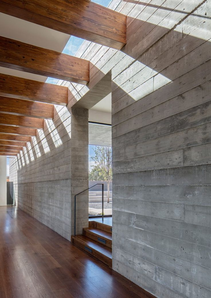 """""""This ridge-top house in Santa Fe is organised around a pair of perpendicular concrete walls that orient the house toward specific views,"""" said the firm, which has offices in Austin and New York.    The longer partition extends from the north to the south, defining the limit of the lower vestibule and cutting through part of the raised terrace."""