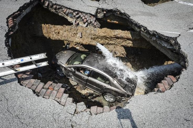 This photo provided by the Toledo, Ohio Fire and Rescue Department shows a car at the bottom of a sinkhole caused by a broken water line in Toledo, Ohio on Wednesday, July 3, 2013. Police say the driver, 60-year-old Pamela Knox of Toledo, was shaken up and didn't appear hurt but was taken to a hospital as a precaution. (AP Photo/Toledo, Ohio Fire and Rescue Department, Lt. Matthew Hertzfeld)Pamela Knox, Ohio Sinkhole, Driver Climbing, Toledo Ohio, Broken Water, Earth Open, Sinks Hole, Swallows Cars, Sinkhole Swallows