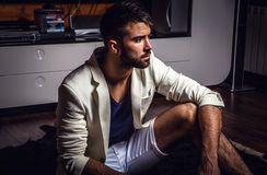 I giovani uomini barbuti attraenti in vestito bianco posano nella stanza moderna Fotografia Stock