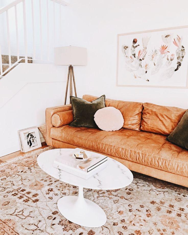 Retro living room: camel leather sofa and dark green velvet pillows
