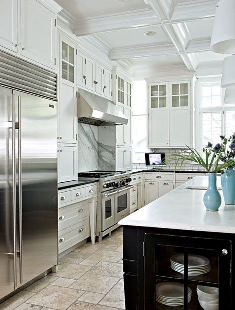 White kitchen island worktop. Black work surfaces. White and grey cooker splashback. Huge stainless steel fridge and oven hood.