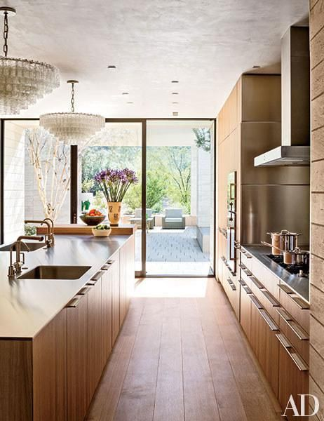 A sunlit Paradise Valley, Arizona, kitchen is outfitted with Boffi cabinetry, countertops, sinks, and sink fittings. The light fixtures are vintage Murano glass, and the floors are of white-oak.