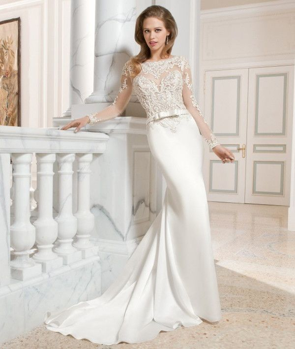 This sophisticated, form fitting, luxe satin wedding gown features exquisite embellished embroidery on the bodice and sheer long sleeves. The dramatic illusion back features accents of beaded embroidery and a button closure.