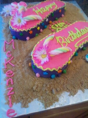 """I made this cake for McK's 8th birthday party  Make any cake in a 9x13 pan, trace an adult flip flop onto paper and cut out to use for your template. Decorate away! The """"thong"""" parts are marshmallow ropes and the """"sand"""" is brown sugar. Cut marshmallows into discs and dip the sticky part into color sugar, arrange like hawaiian flowers! So much fun to do!"""
