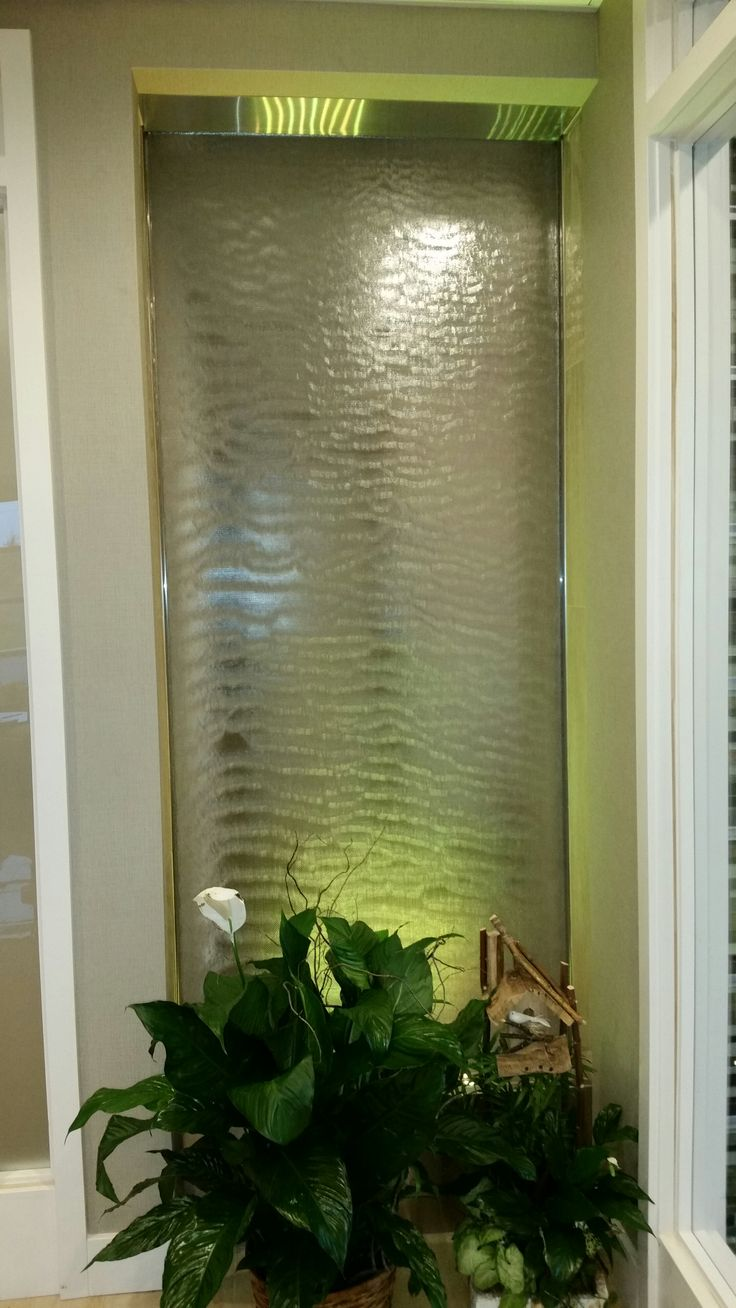 Indoor stainless steel waterwall with stainless mesh face and color changing LED lighting. built by Pondering Waters, LLC www.indoorwaterfalldesign.com