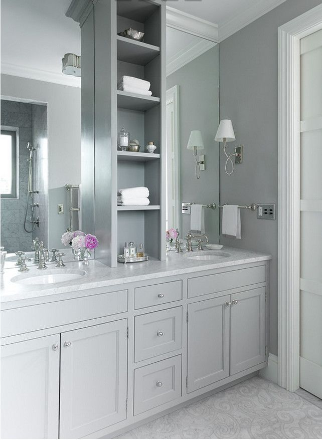 Gray Bathroom. Grey master bathroom features gray shaker washstands topped with white marble fitted with his and her sinks under full height frameless mirrors flanking a grey shelving unit alongside a mosaic marble floor.  Jenny Wolf Interiors.