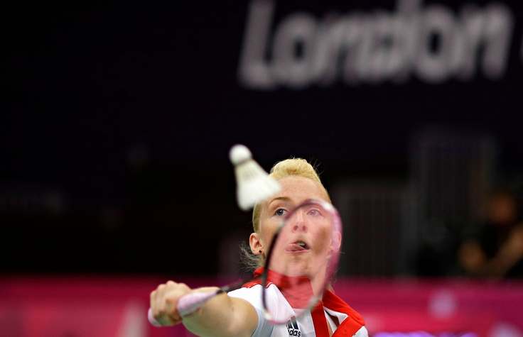 Imogen Bankier of Great Britain returned a shuttle cock while playing against Valeria Sorokina and Alexandr Nikolaenko of Russia, unseen, at a mixed doubles badminton match. Bankier's partner, Chris Adcock, is also unseen. The Russians won the best-of-three match, 2-1.
