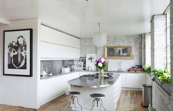 Elegante Küche in Weiß mit unbehandelter Ziegelwand