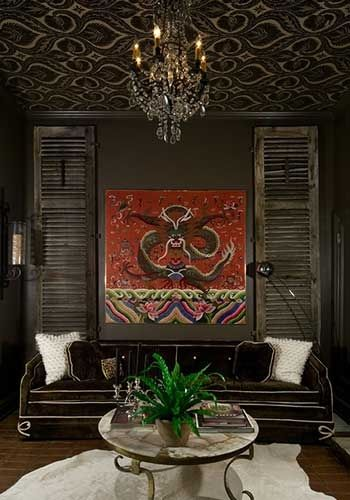 wallpapered ceiling chocolate brown walls rustic shutters white cowhide rug driscoll design