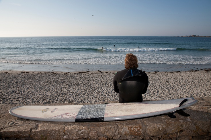 Surfer relaxing at Vazon Bay, Guernsey.