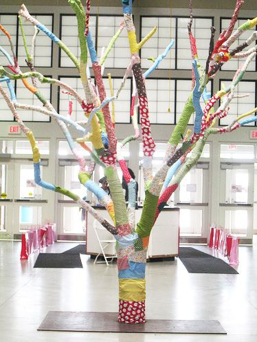 "Tree Wrap ~ ""I love fabric.  It's patchwork here, calico there and the color just makes us happy.  Our wheels were spinning when we discovered a barren tree at the fairgrounds.  So, we wrapped it up with the most colorful fabric..."""