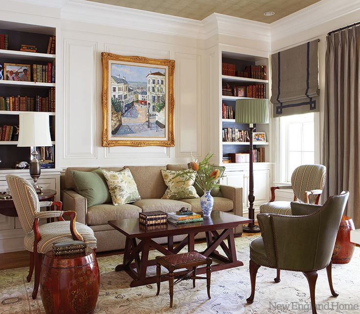 Greenwich designer Amy Aidinis Hirsch refurbished this homeowner's existing chairs for the library. Montmartre, by Jacques Bouyssou, hangs above a sofa strewn with floral-patterned pillows. Photo by Michael Partenio
