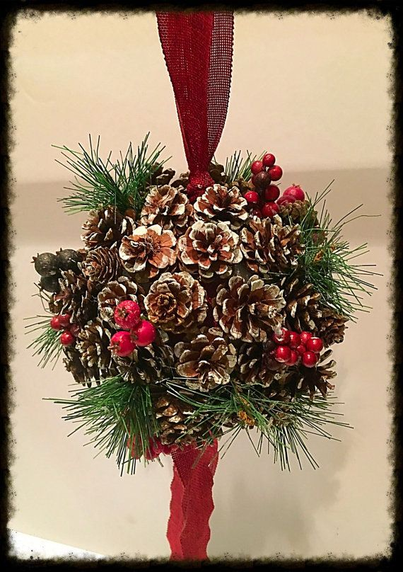 This is a great alternative to mistletoe and makes a stunning addition to your winter and Christmas decorations! Made with artificial, white tipped pine cones, greenery and berries, it can be stored and used for years to come!!  Measures approximately 6 in diameter and hangs 21 from the top of the ribbon loop to the bottom.  If you need more than 1 just place a custom order, Ill be happy to oblige