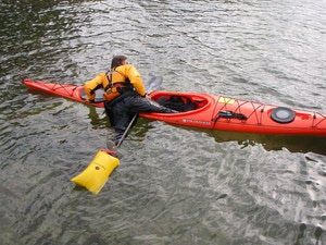 How to properly use a paddle float to get back into and bilge out a flipped kayak. - © by George E. Sayour