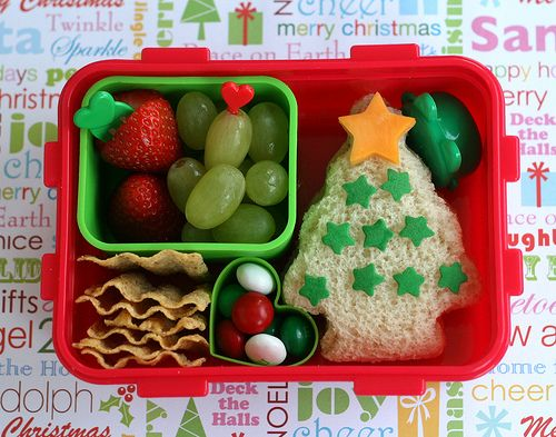 Packed in a bento box as rosy as Santa's cheeks is a green dish of strawberries and grapes, a Christmas tree sandwich (decorated with cheese star and sprinkles), some SunChips, the tiny green cup in the corner holds sunflower kernels and the pièce de résistance: heart-shaped mini cup lovingly cradling the beloved Christmas colored mint M's.