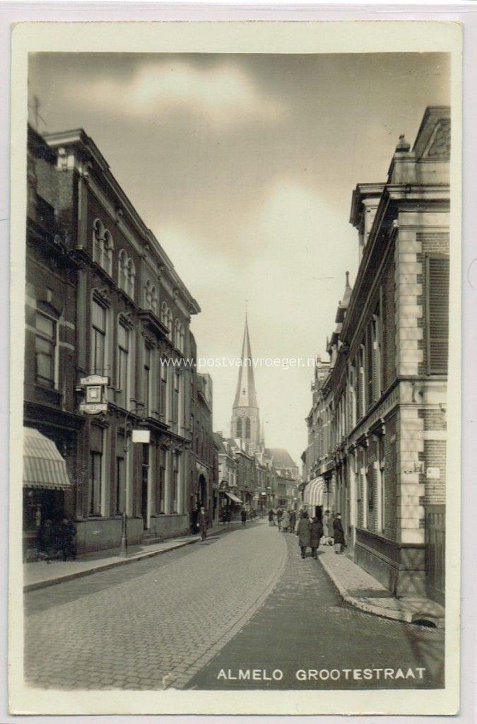 """Almelo, Grotestraat Noord, gezien vanaf de Kerkstraat. Links het hoge pand van Bendien """"met de hoge stoep"""", waar begin jaren '70 bar-discotheek 't Stuupke in heeft gezeten en er boven in de jaren '60 Judo-sportschool Bouter."""