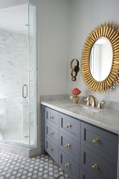 Gorgeous bathroom with gray vanity accented with brass hardware.
