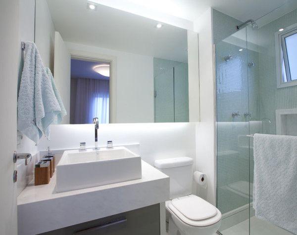 Detalhe: iluminação. Banheiro todo branco com espelho colado no painel + iluminação embutida. Nesse caso foi usado lâmpada fluorescente, por isso a intensidade da luz é maior e também existe uma pequena sombra nos cantos, onde a lâmpada não chega por causa dos acabamentos.