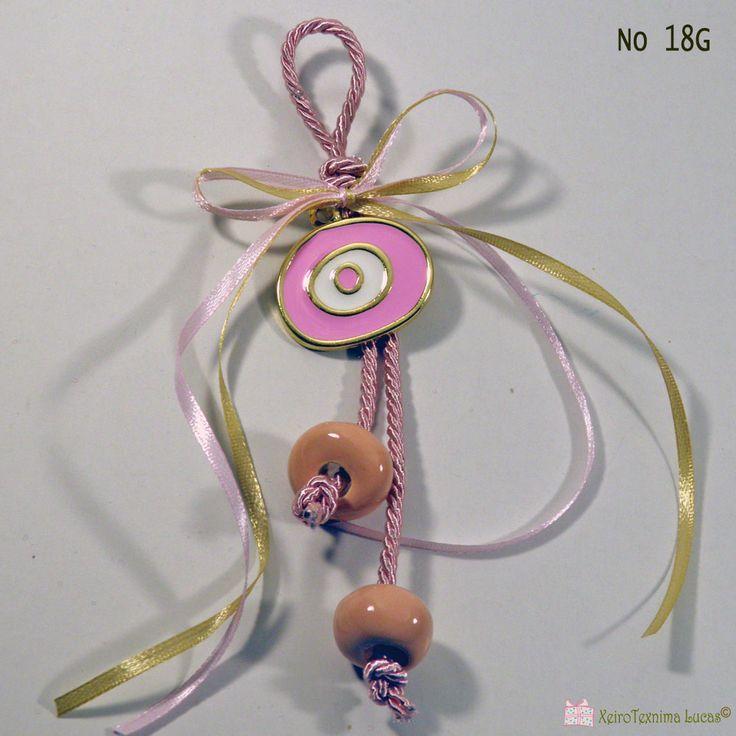 Γούρι με μεταλλικό μάτι με σμάλτο σε διάφορα χρώματα διακοσμημένο με τρίκλωνο κορδόνι και χειροποίητες κεραμικές χάντρες. Metal evil eye charm with enamel in many colors decorated with handmade ceramic beads.