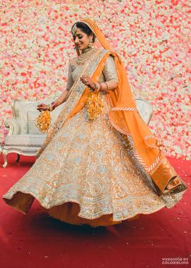 Bridal Lehenga - Gursimran & Meher wedding story | WedMeGood | Twirling Bride in a Silver and Orange Lehenga with Orange Pom Pom Kallere  #wedmegood #indianbride #indianwedding #bridal #lehenga #orange #silver #bridallehenga