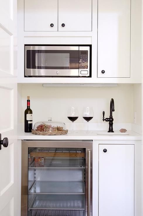 Small, chic butler's pantry features creamy white inset cabinets adorned with bronze knobs fitted with an over the counter microwave.