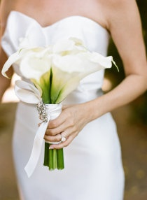 Brides white calla lillies bouquet tied with white ribbon
