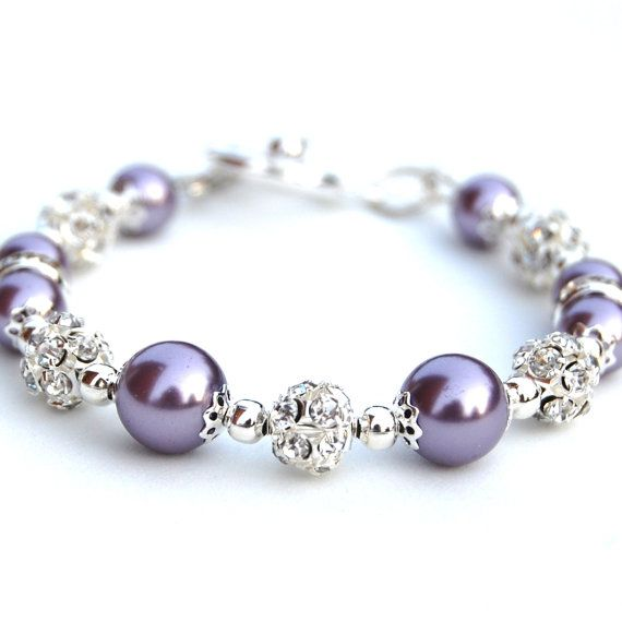 Lavender purple pearls and rhinestones sparkle in this perfect gift for her. I have strung 8 and 10mm glass pearls with 8mm rhinestone fireballs and rondelles. Small silver plate seed beads are used as spacers.  The bracelet is finished with a silver plate toggle clasp and measures 7.5/19cm. If you need the length adjusted, just put the desired length in the message to seller. Like this bracelet but prefer a different colour? Check out my other bling pearl bracelets here - http:/&#x...