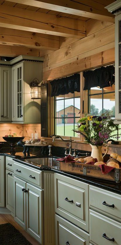 FARMHOUSE – INTERIOR – vintage early american farmhouse showcases raised panel walls, barn wood floor, exposed beamed ceiling, and a simple style for moulding and trim, like in this farmhouse kitchen with very pretty cabinets.