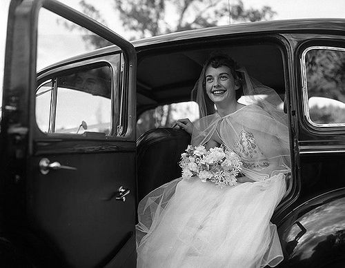 Caption: Bride dressed in wedding gown, holding a bouquet, getting out of a car. Photographer: Unknown  Synopsis: A humorous look at Melbourne. Production Company: Department of Information  Producer: Ron Maslyn Williams Director: Colin Dean Cinematographer: R.G. Pearse  FAC Accession Number: MWB_2 Copyright: Film Australia Collection © NFSA For information about licensing reproductions of photographs held by the NFSA's Film Australia Collection, visit…