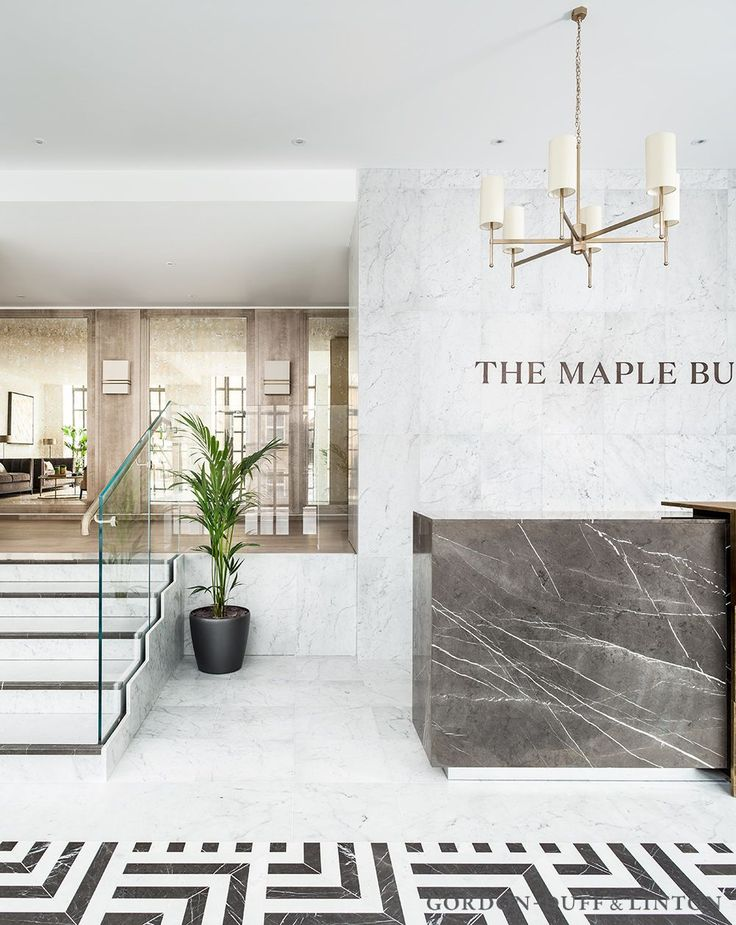 Reception featuring grey marquina and white carrara marble geometric patterned tiles. The bespoke reception desk is clad in grey marquina marble and sold brass central section. The mezzanine level has antique mirror panels. The pendants are from Tigermoth.  #GD&LBespokeFurniture