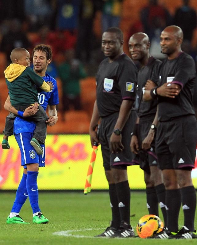 Brazil's Neymar, holds unidentified child at the end of their international friendly soccer match against South Africa during their international friendly soccer match at Soccer City Stadium in Johannesburg, South Africa, Wednesday, March 5, 2014. Brazil beat South Africa 5-0