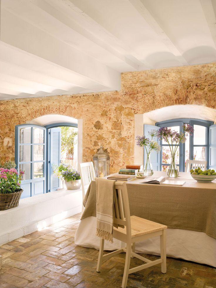 Comedor en casa rústica con paredes de piedra vista_317251