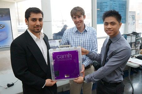 George Brown College students Rashid Karimi (left) and Jackson Quang (right) collaborated with Dr. Sean Kidd (centre) to develop an automated pill dispenser that not only gives out the correct dose of medication and reminds patients to take it, but also signals if a dispensed dose is missed.