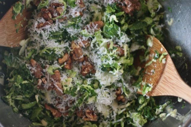 raw kale and brussels sprout salad topped with toasted walnuts and ...