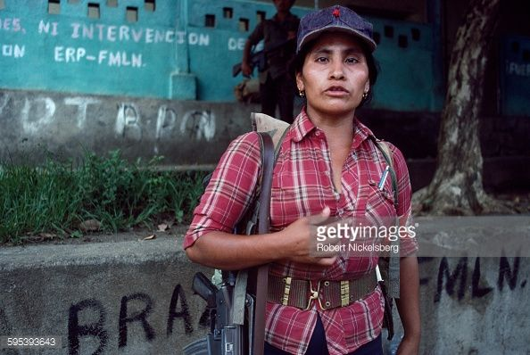 Robert Nickelsberg, San Miguel, El Salvador, 1983. Portrait of a Popular Revolutionary Forces (ERP) guerrilla as she stands in front of a Salvadoran government building occupied during an attack, San Miguel, El Salvador, September 1, 1983. At the time, the country was engaged in what became a 13-year Civil War between successive right-wing governments (backed by the US and others) and various armed guerrilla factions that eventually claimed over 75,000 lives before ending in 1992.