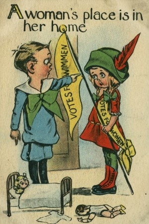 """This is an anti-suffrage post card showing that many men believe that women belong in their houses and not out in the real world. Women fought hard to gain rights during this time period and suffered through much pain of having very few rights. In this photo this women is dressed and holding a flag showing she has been fighting for women's rights, while the boy is telling her that """"A women's place is in her home""""  Thomas St. Clair"""