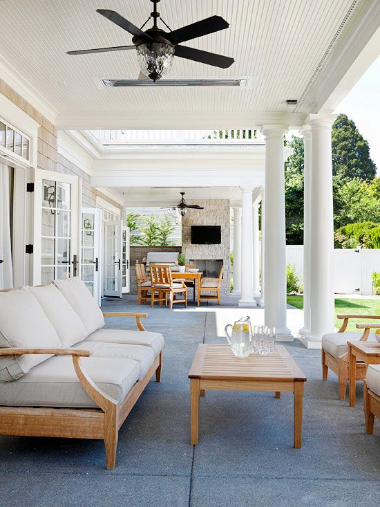 Open Spaces_This large concrete patio is the perfect space for summertime entertaining. On one side, a dining table and chairs benefit from a grill and an outdoor fireplace. On the other side, an arrangement of teak furniture offers a cozy space to relax and chat with guests. Ceiling fans installed in both sections help circulate the air.