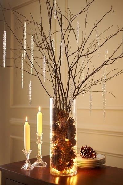 Pine cones, white Christmas lights & tree branches inside a clear, tall vase.