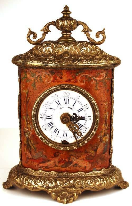 Antique Nineteenth Century French Carriage Clock - The heavy case is made of cast bronze. The top has an urn, flanked by two scrolling arabesques. The center body is painted & though faded with time, cherubs, flowers & scrolls can still be seen.  The movement winds from the back with one key for the time and another for the alarm. The porcelain face has Roman numerals for the hours and cardinal numbers for the minutes.