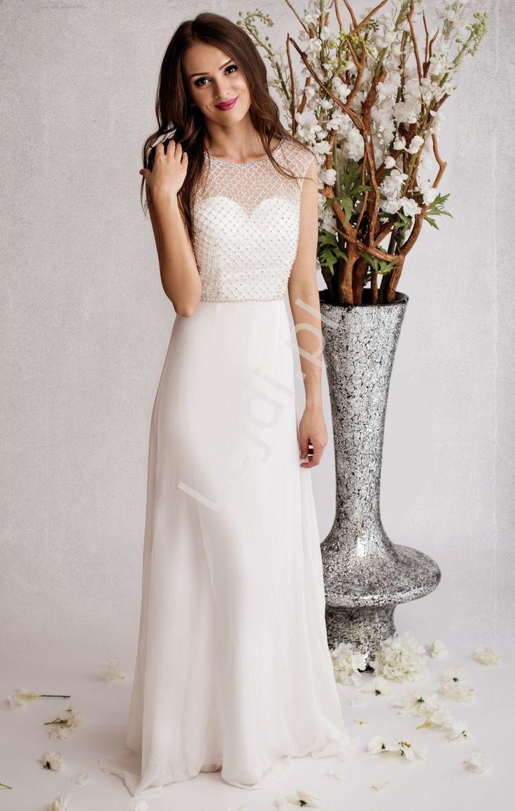 Suknia ślubna z bogato zdobioną górą, siatka przepięknie mieniąca, wyszyta kryształkami na przodzie, natomiast tył wyszyty drobnymi koralikami złączony na górze paseczkiem. Suknia długa, luźno opływająca biodra.