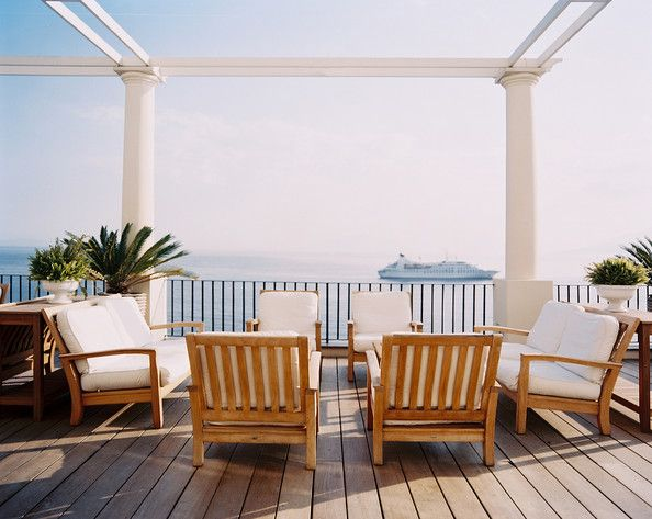 Outdoor furniture with white cushions on a deck overlooking the ocean