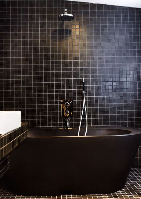 Black tiles and fittings lend the bathroom a dramatic look. The black bathtub is made of recycled plastic.