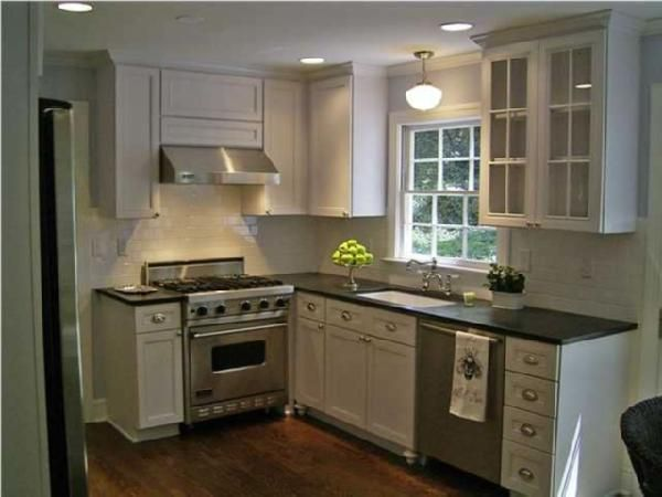 Small kitchen inspiration  glass-front white kitchen cabinets, black coutertops, school house lights... right up my alley.