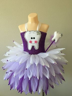 This is the perfect Halloween costume for the little Tooth fairy in your life. This listing is for the purple tooth fairy. The colors are purple, lavender and white. This listing includes the pixie style fairy inspired tutu dress embellished with a custom made tooth appliqué and rhinestones AND rhinestone embellished fairy wings. This tutu dress is made with layers and layers of tulle to be super cute and fluffy. The tutu dress is done pixie style and is accented with rhinestone tips. It is…