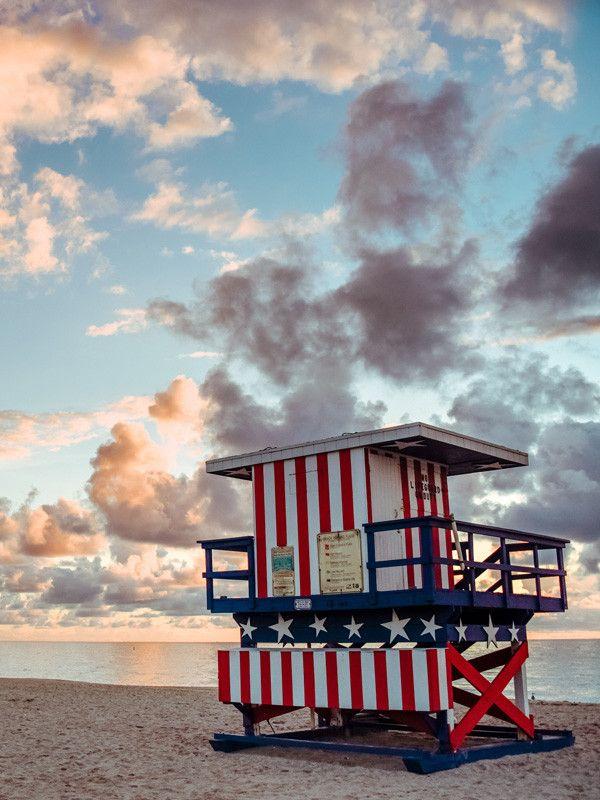 Sunrise over American flag lifeguard tower