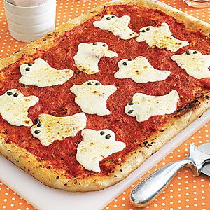 Frozen pizza dough is the secret to this easy pizza which is topped with slices of mozzarella cheese shaped like ghosts.