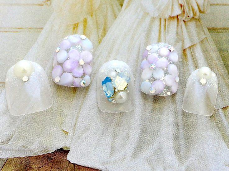 花嫁の清らかさをイメージした淡いブルーとパープルのお花と「夫への忠義の証」サムシングブルーのブライダル・ウェディングネイルです。